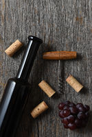Wine Bottle on a rustic old wood table with grapes, corkscrew and corks. Vertical with copy space.