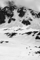 Black and white high mountain with snow cornice and avalanche trail