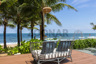An outdoor rattan sofa on a terrace facing the beach