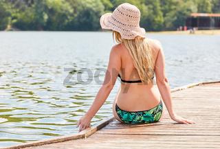 Junge Frau auf einem Holzsteg am Badesee