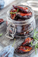 Jar with dried plum, spices, olive oil and rosemary.