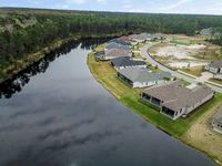 Houes and Screen Porches Line the Bank of a Small Pond in an American Neighborhood from Above Aerial