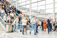 Viele anonyme Menschen auf Rolltreppe einer Messe