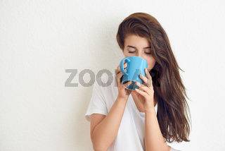 Smiling woman drinking coffee from blue mug