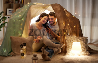 happy couple with smartphone in kids tent at home