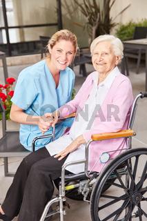 Altenpflegerin und Seniorin im Rollstuhl