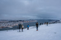 Tourists photographing Tromso town in winter