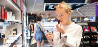 Beautiful blond young woman choosing perfume in retail store. Lady testing and buying cosmetics in beauty store