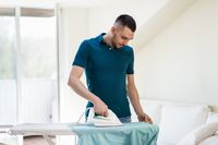 man ironing shirt by iron at home