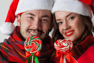 Couple in christmas santa hats with lollipops
