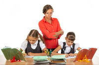 A strict teacher stands above the children who solve the task