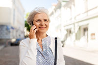 senior woman calling on smartphone in city