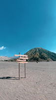 Wood sign and beautiful Mount Bromo volcano with desert in East Java