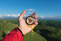 Man searching direction with a compass in his hand in the summer mountains point of view. Direction Search