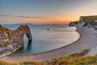 The natural arch Durdle Door at the Jurassic Coast in England at sunset
