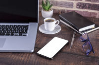 Laptop notebook with blank screen and cup of coffee and notepad pen and books and smart-phone on wooden