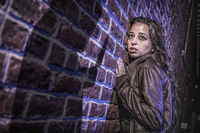 Male Shadow Figure With Knife Threatens Frightened Young Woman Against Brick Wall