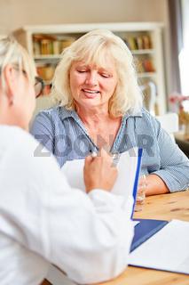 Ärztin mit Patientenakte bei der Anamnese