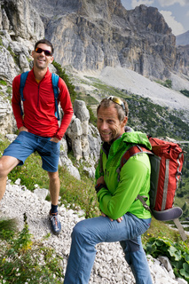 two mountain guides smiling and having a look at the climbing route before them