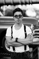 Guy in a shirt with suspenders posing at the retro car