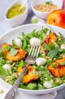 Salad with arugula, nectarines and pesto sauce.