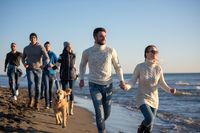 Group of friends running on beach during autumn day