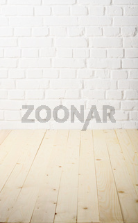 White brick wall of painted genuine clay blocks and wooden floor background