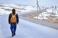 Traveller wearing backpack and walking along rural highway