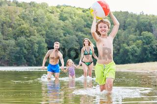 Junge läuft mit einem Ball durchs Wasser