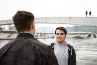 two male teenage friends having a conversation by the river
