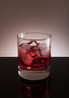 Red cocktail with ice in the transparent glass, isolated