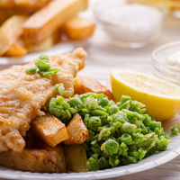 Traditional British street food fish and chips with tartar sauce and mushy peas on paper plate