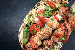 Traditional Greek souvlaki barbecue skewer with tomato