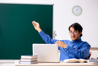 Young male teacher in front of chalkboard