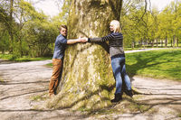 nature loving young couple hugging tree trunk