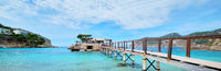 Wooden walkway leading across turquoise Mediterranean Sea panoramic image