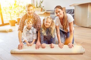 Eltern und Kinder rollen Teppich beim Umzug