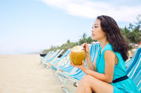 Young beautiful asian woman is drinking coconut juice on the tropical sea beach