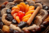 Mix of dried fruits in a small wicker basket on wooden table