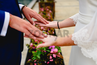 Newly-married couple stroking the palms of their hands.