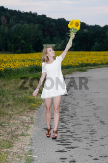 Young woman in white dress with sunflowers