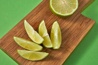 Natural organic citrus fruit - slices of of green organic lime on a wooden board on green.
