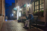 Figure of a sailor on a bench in front of a pub.