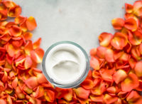 Beauty face moisturizing cream and flower petals on marble, luxury cosmetic product