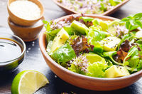 Clay dish with salad of avocado, green and violet lettuce, lamb's lettuce and oregano flowers on slate stone tray with soy sauce and lime and sesame