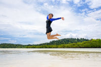 Happy asian teen girl jumping fun on the beach