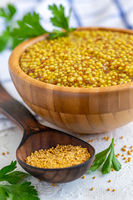 Grain mustard in a wooden bowl close-up.