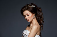 beautiful bride in wedding gown on grey background