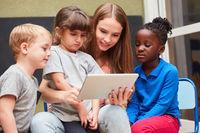 Kinder und Lehrerin lesen in einem Ebook