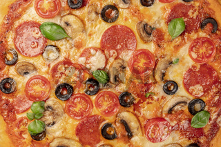 Pepperoni pizza texture with vibrant salami slices, black olives, mushrooms, fresh basil leaves and a lot of cheese